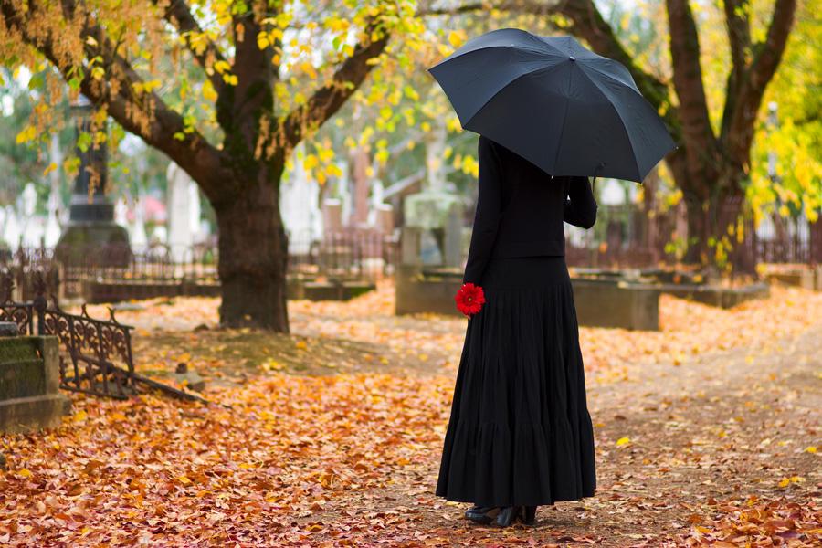 vrouw-in-zwart-rode-bloem-begraafplaats-herdenken-rouw-begrafenis-uitvaart